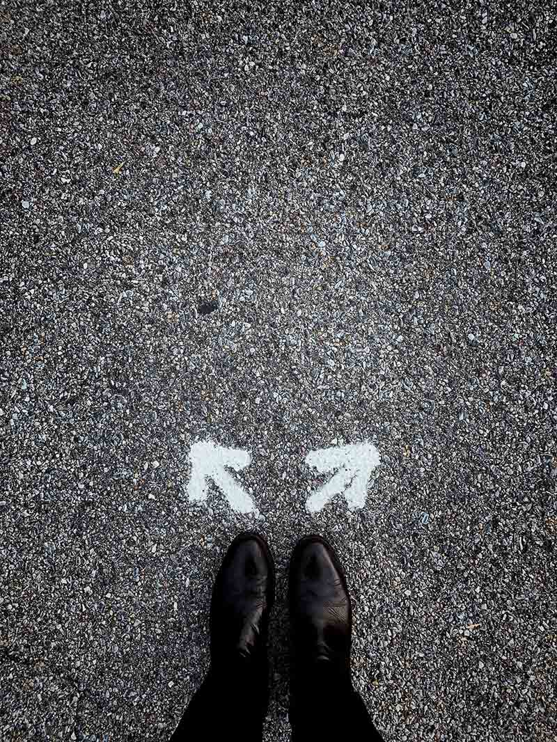photo d'un chemin avec 2 flèches indiquant 2 directions différentes